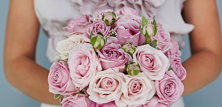 Frau die rosa Rosenstrauß in den Händen hält
