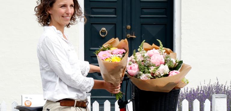 Frau auf Fahrrad mit Blumenstrauß im Körbchen