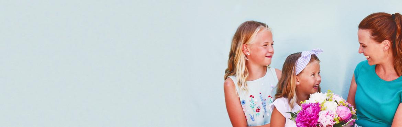 Muttertagspezial: zwei Mädchen geben Ihrer Mutter einen Blumenstrauß